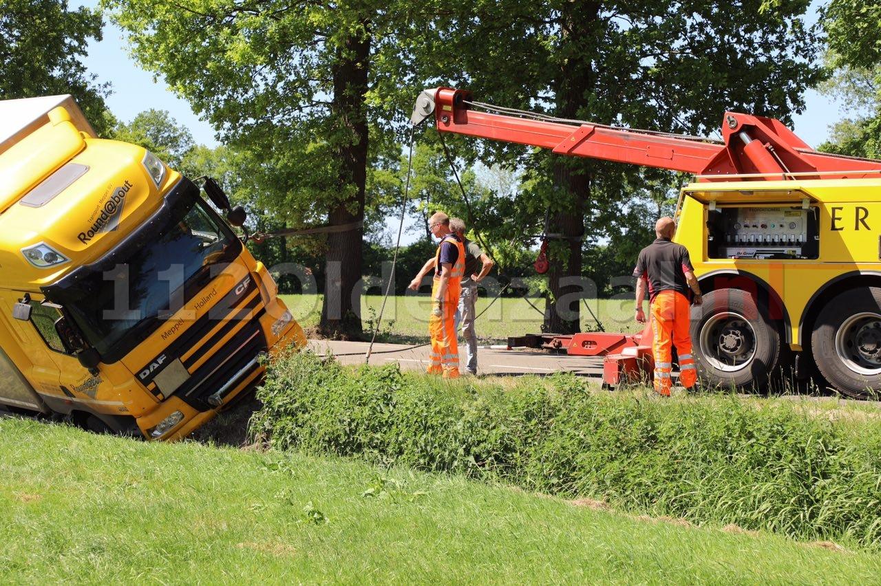 Vrachtwagen op zijn zijkant in sloot Saasveld